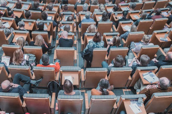 foto de pessoas em uma conferência, representando os materiais gráficos para eventos
