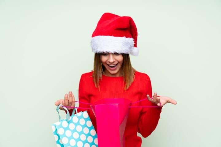 foto de uma mulher abrindo presentes, representando os materiais gráficos para o Natal
