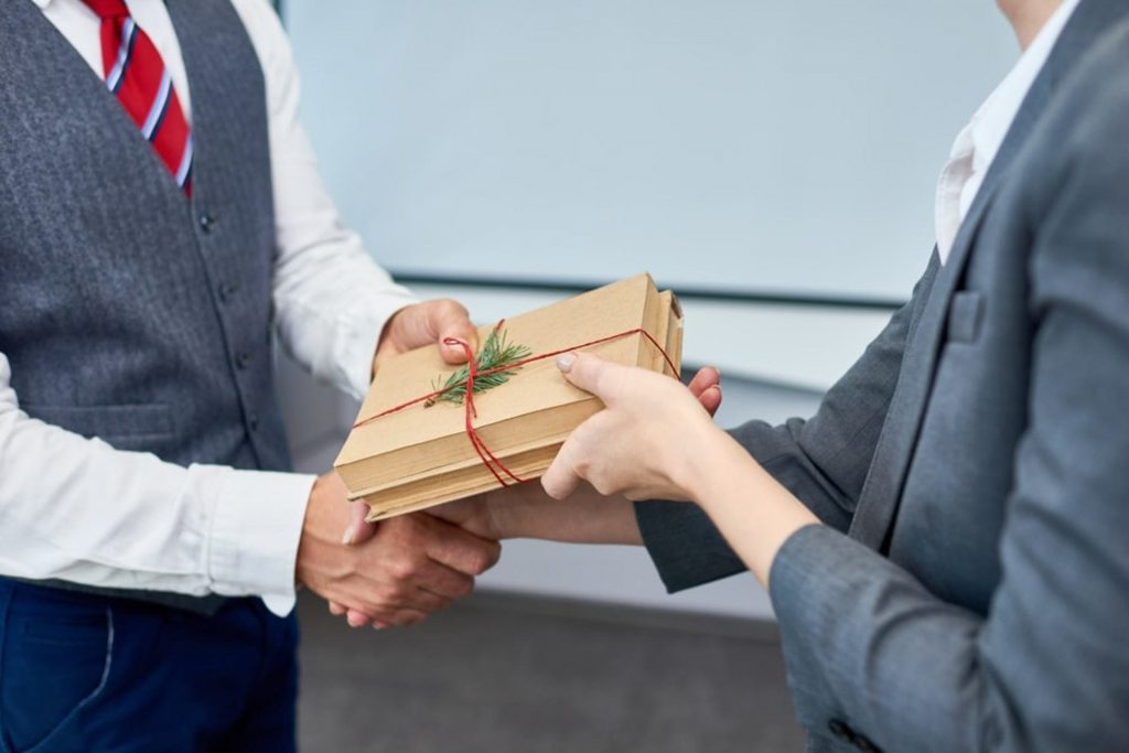 foto de uma pessoa entregando brindes de fim de ano para outra