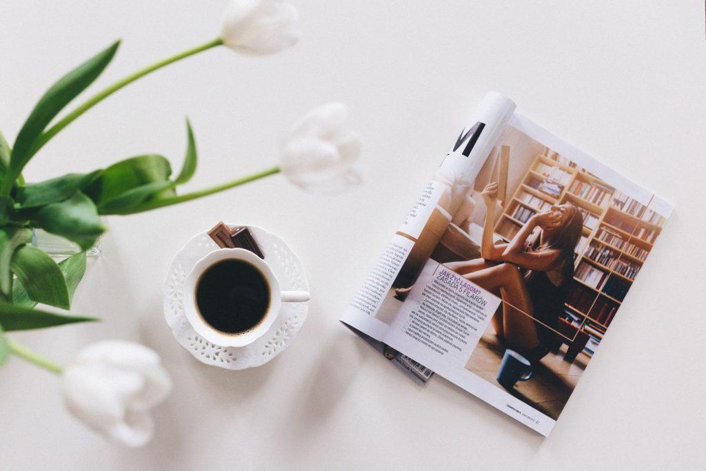 foto de uma revista ao lado de uma xicara de café representando como criar uma revista