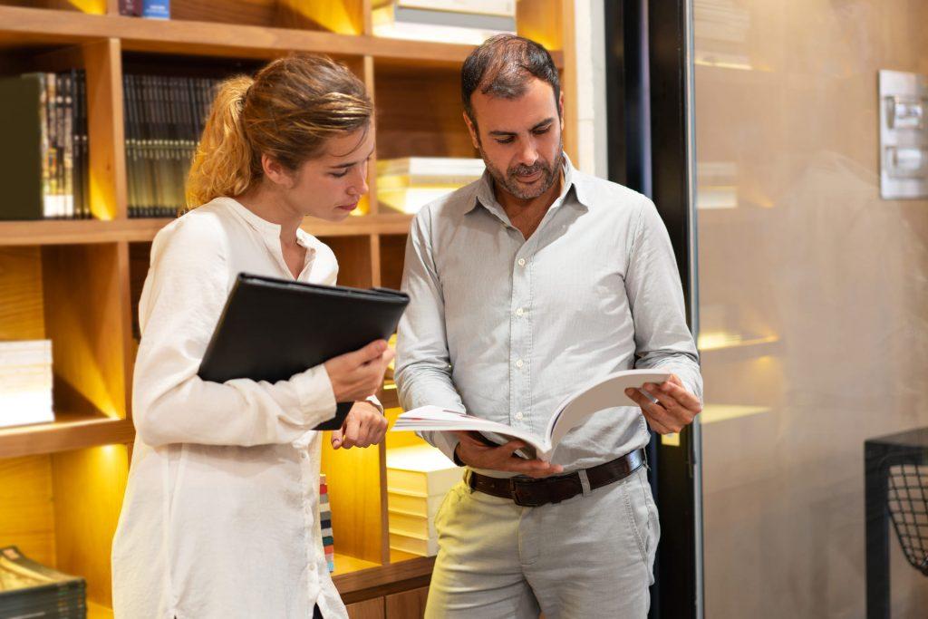 foto de duas pessoas olhando uma revista corporativa no escritório