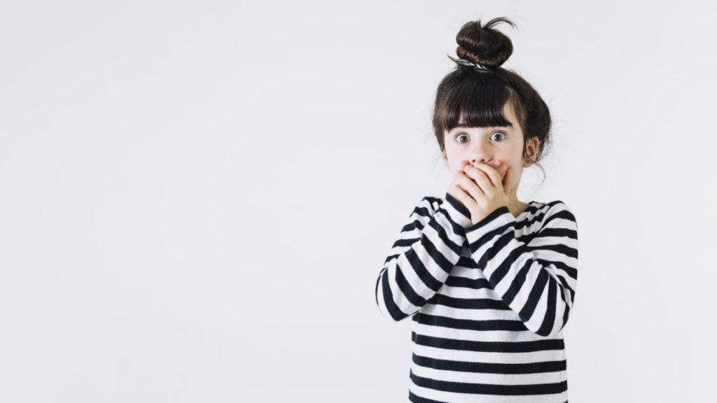 foto de garota com a mão na boca, representando