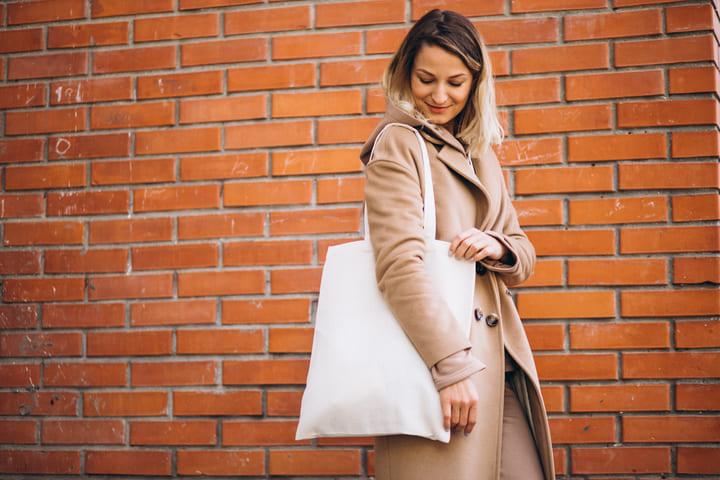 mulher usando sacolas promocionais do tipo ecobag